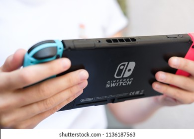 Anapa, Russian Federation - 17 July 2018,  Teenager girl playing game on Nintendo Switch console. Female hands with handheld Nintendo Switch. Close up