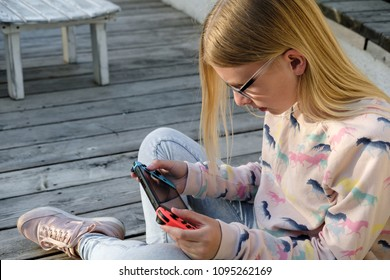 Anapa, Russian Federation - 2 May 2018,  Teenager girl playing game on Nintendo Switch console. Kid with handheld Nintendo Switch outdoor