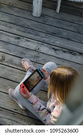 Anapa, Russian Federation - 2 May 2018,  Teenager girl playing game on Nintendo Switch console. Kid with handheld Nintendo Switch outdoor. Top view