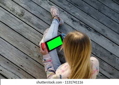 Anapa, Russian Federation - 2 May 2018, Teenager girl playing game on Nintendo Switch console. Kid with handheld Nintendo Switch outdoor. green screen