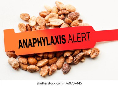 Anaphylaxis alert bracelet over peanuts on white background