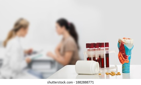 Anatomical model of thyroid gland and blood in test tubes for the analysis of hormones on doctor's table, close-up. Endocrinologist consulting a patient with endocrinological disease