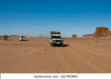 ancars driving through the Sahara desert, Chad, Africa.