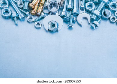 Anchor bolts screwbolts nuts hook wrenches and flat spanner on metallic background construction concept
