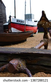 Anchor in the foreground. Fisher boat and fisher huts in the background. Beach of Hastings.