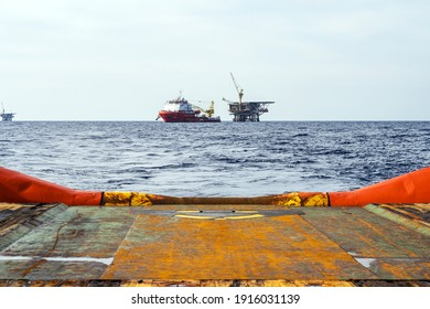 An anchor handling tug boat leaving an offshore oil production platform with a construction vessel moored next to it - Shutterstock ID 1916031139