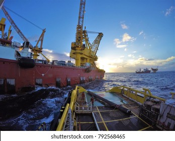 Anchor handling tug delivering pipe to derrick lay vessel during offshore installation work