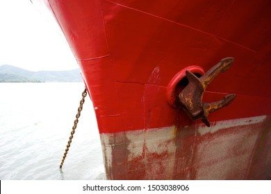 Anchor on red ship close-up. Rusty anchor on bow of ferryboat or tanker. Detail of marine vessel with big anchor in sea port.