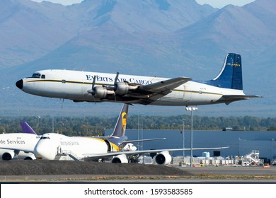 Anchorage, AK / USA - September 12 2018: Everts Air Cargo Douglas DC-6 low level departure in Alaska. Four piston engines plane registered as N151. Vintage airplane flying cargo operations.
