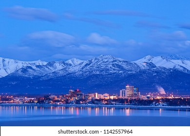Anchorage Alaska skyline in winter at dusk with the Chugach mountains behind.
