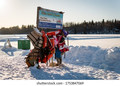 "Anchorage, Alaska / USA - February 6, 2020: ""Kids Don't Float! Give Them Something That Does"" warning sign in Margaret Eagan Sullivan Park, & Westchester Lagoon. Life vests hang from information board"