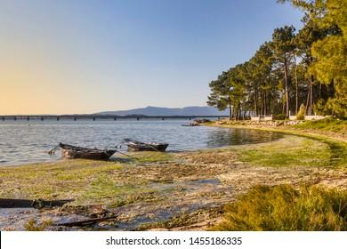 Anchored boats and algae accumulated at hight tide on Patinas beach in Vilanova de Arousa
