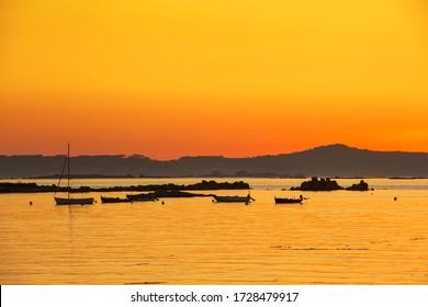 Anchored boats in Arousa estuary at golden dusk with Rua island lighthouse lighting