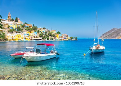 Anchored boats and colorful neoclassical houses in bay of Symi (Symi Island, Greece)
