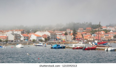 Anchored boats and Illa de Arousa seafront in the fog