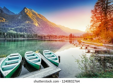 Anchored Boats on Lake Hintersee - Picturesque sunset scenery of Alpine nature in Germany, Bavaria, Europe. Autumn Landscape. Mountain peaks in backdrop, Berchtesgaden National Park, Ramsau.