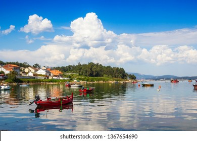 Anchored boats on Naval fishing harbor in Arousa Island with cumulus clouds on the sky