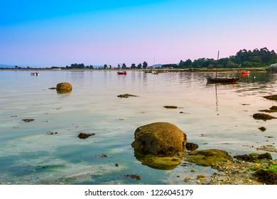 Anchored boats on Riason beach, Arousa Island, with calm sea at the evening