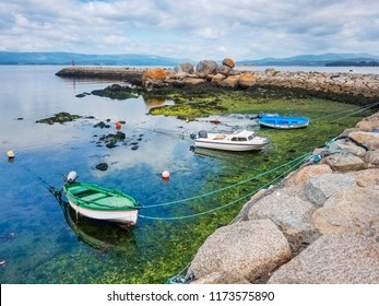 Anchored boats protected by the breakwater at low tide in Vilaxoan harbor, Vilagarcia de Arousa