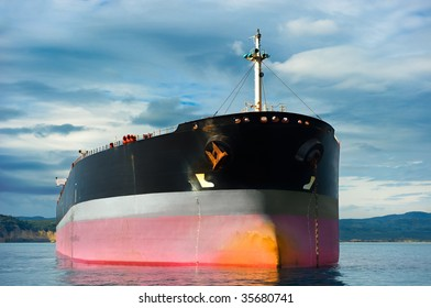 Anchored empty tanker ship under an overcast sky