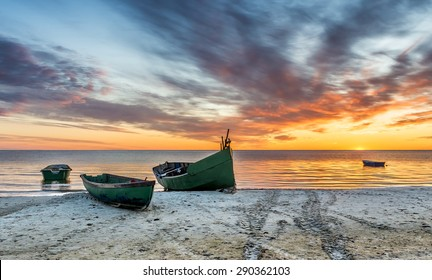 Anchored fishing boat on sandy beach of the Baltic Sea