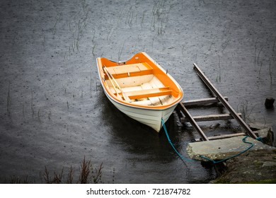 Anchored Orange rowing boat on a rainy day in the lake