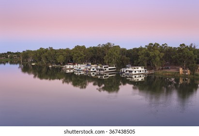 anchored residential river house boats docked on Murray river at VIC NSW border in Australia during sunrise hour