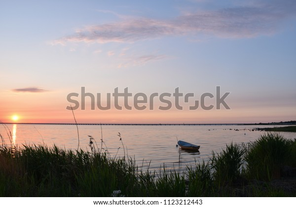 Anchored small rowing boat in a bay by sunset with the Oland Bridge in the background