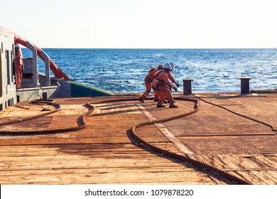 Anchor-handling Tug Supply AHTS vessel crew preparing vessel for static tow tanker lifting. Ocean tug job. 3 AB and Bosun on deck. They pull towing wire