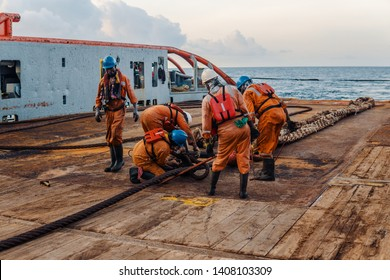 Anchor-handling Tug Supply AHTS vessel crew preparing vessel for static tow tanker lifting. Ocean tug job. AB and Bosun on deck. They pull towing wire