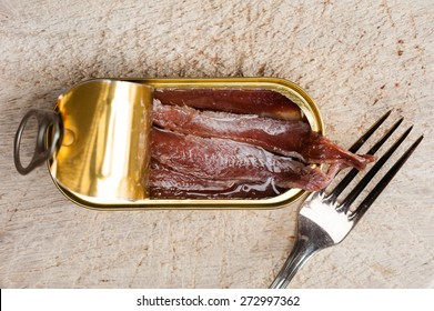 Anchovies in an opened tin can on wood, with a fork
