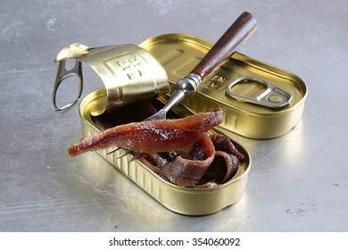 Anchovy in an opened tin can on metal, with a fork
