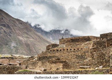 Ancient abandoned Inca Fortress with lonely man sitting and cloudy mountains at background in Ollantaytambo, Peru.