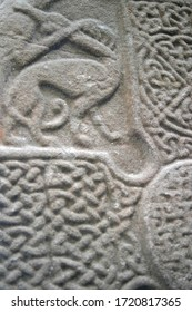 Ancient abstract design carved onto a standing stone in northern europe.  Shows animal possiblybeing hunted beside a celic cross