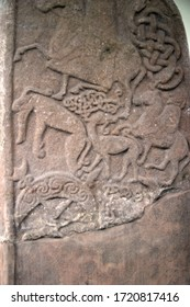 Ancient abstract design carved onto a standing stone in northern europe.  Shows animals and riders on horses possibly hunting.