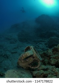ancient amphora underwater sun behind scenery