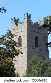 Ancient angular stone tower with trees, Dublin, Ireland.