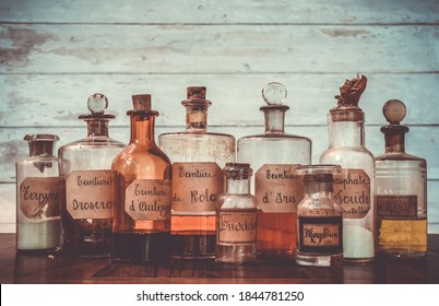 ancient apothecary jars with ingredients in french for medicine isolated over white wooden background. translation : Terpine powder, Drosera and aubepine tincture, kola tincture, Iris essential oil