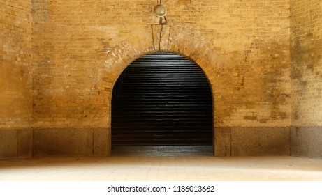 Ancient arch in a wall with yellow brick and stairs.
