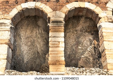 Ancient arch windows in a Roman stone wall in the center of Verona, Italy. Detail of a historic exterior brick wall.
