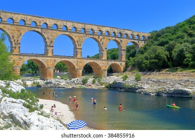 Ancient arches of Pont du Gard and people swimming on the river near Nimes, France