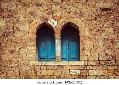 Ancient architecture background, two little windows with blue wooden shutters among great stony wall, house of God, old monastery, Lebanon