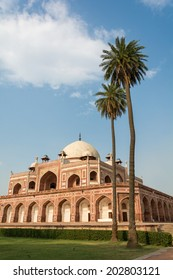 Ancient architecture in India with palm trees in the foreground
