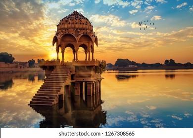 Ancient architecture ruins at Gadi Sagar (Gadisar) lake Jaipur Rajasthan at sunrise with vibrant moody sky.