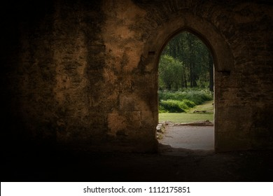 Ancient archway frames summer garden beyond.  Thought provoking image with high contract is colours.