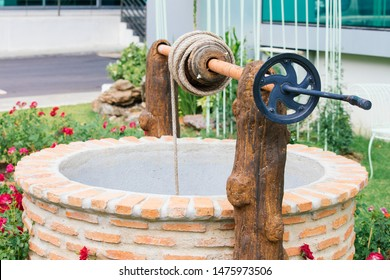 Ancient artesian well made by bricks and wheel pulley  in the garden