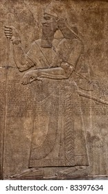 Ancient assyrian clay relief depicting a warrior with a sword and text written in cuneiform writing