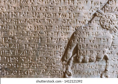 ancient Assyrian cuneiform carved on stone wall