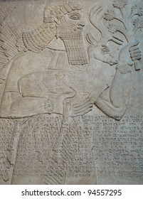 Ancient Assyrian wall carvings of a man and cuneiform writing