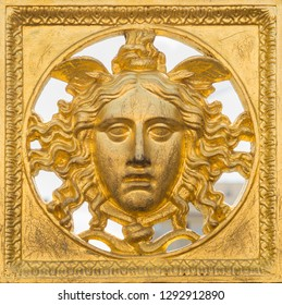 Ancient baroque golden mask on a fence at Palazzo Reale, Turin, Italy